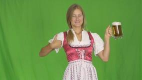 Mädchen im bayerischen nationalen Kostüm mit Becher Bier Oktoberfest auf grünem Schirm stock video