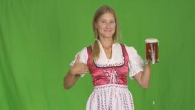 Mädchen im bayerischen nationalen Kostüm mit Bier auf grünem Hintergrund stock video footage