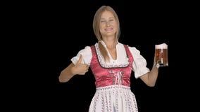 Mädchen im bayerischen nationalen Kostüm trinkt Bier und zeigt Daumen lokalisierten Hintergrund stock video footage