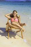 Mädchen im Bikini auf einem Strandstuhl Stockfoto