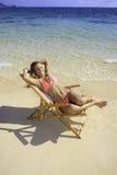 Mädchen im Bikini auf einem Strandstuhl Lizenzfreie Stockbilder