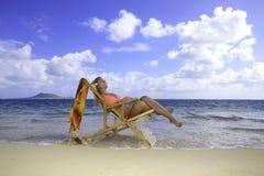 Mädchen im Bikini auf einem Strandstuhl Lizenzfreies Stockfoto