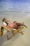 Mädchen im Bikini auf einem Strandstuhl Stockbilder