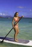 Mädchen im Bikini auf ihrem Paddelvorstand Stockfotografie
