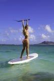 Mädchen im Bikini auf ihrem Paddelvorstand Stockbild