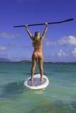 Mädchen im Bikini auf ihrem Paddelvorstand Lizenzfreie Stockbilder