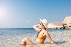 Mädchen im Bikini, in den Gläsern und im Hut im klaren Meerwasser Stockfoto