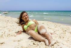 Mädchen im Bikini, der auf dem Sand auf dem Strand auf dem sonnigen Meer liegt Stockbild