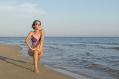 Mädchen im Bikini, der am Strand ausdehnt und trainiert Lizenzfreie Stockfotos