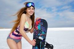 Mädchen im Bikini mit Snowboard Stockfoto