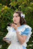 Mädchen im Bild der fabelhaften Heldin trinkt Tee Lizenzfreie Stockfotos