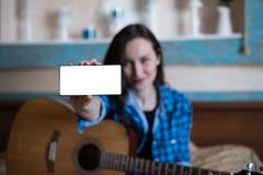 Mädchen im blauen Hemd und in den Jeans mit Akustikgitarre zeigt Hand mit Smartphone mit Kopienraum, Spott oben das blogging Konz Lizenzfreies Stockbild