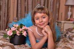 Mädchen im blauen Kleid, das auf einem Sofa stillsteht Lizenzfreie Stockfotografie