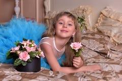 Mädchen im blauen Kleid, das auf einem Sofa stillsteht Lizenzfreie Stockbilder