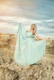 Mädchen im blauen Kleid im Sand Lizenzfreies Stockbild