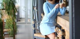 Mädchen im blauen Kleid sitzt an einem Barzähler und trinkt Kaffee Warten auf einen Begleiter, Freund Treffen in einem Café stockfotografie