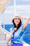 Mädchen im blauen Kleid und Hut haben eine Reise auf einem Boot stockfotografie