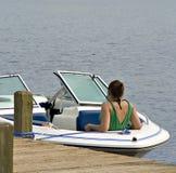 Mädchen im Boot gebunden am Dock Stockfotografie