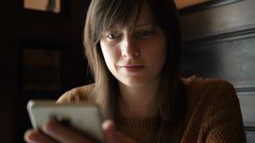 Mädchen im Café mit einem Smartphone in den Händen stock video footage