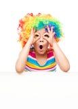 Mädchen im Clown hält leere Fahne Stockfotografie