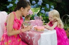 Mädchen im Garten, der kleine Kuchen bereift Lizenzfreie Stockfotografie