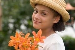 Mädchen im Garten mit Blumen Lizenzfreie Stockfotos