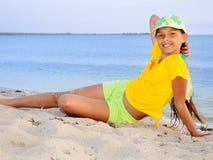 Mädchen im Gelb am Strand Stockfoto