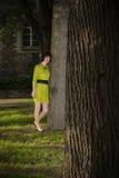 Mädchen im gelben Kleid lehnt sich auf einem Baum in einem Park Stockfotografie