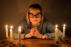 Mädchen im Glas sitzt nahe der Tabelle mit Kerzen in einer Dunkelkammer Lizenzfreie Stockbilder