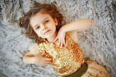 Mädchen im goldenen Kleid auf Pelz stockbilder
