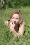 Mädchen im grünen Gras des Sommers Stockbilder
