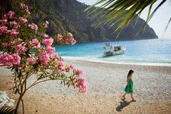 Mädchen im grünen Kleid schlendert den Strand Stockbilder