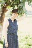 Mädchen im grünen Sommergarten der Apfelbäume Lizenzfreie Stockfotos