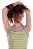 Mädchen im grünen stripy versteckenden Spitzengesicht im Haar. Stockfotografie