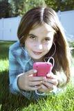 Mädchen im Gras, das Musik hört Lizenzfreies Stockbild