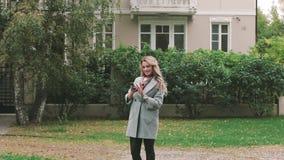 Mädchen im Grau gehend nahe dem Ahorngrünbaum, Herbst aufwerfend stock footage