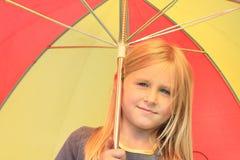 Mädchen im Grau mit rotem und gelbem Regenschirm Stockfotografie