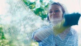 Mädchen im Hemd und in den modernen Kopfhörern wischt schmutziges Fenster ab stock footage