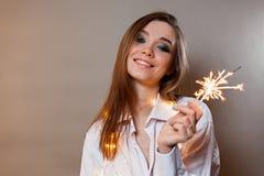 Mädchen im Hemdlächeln mit Wunderkerze stockbild