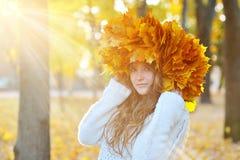 Mädchen im Herbstpark, im Herbstsonnenschein und in einem Kranz von Blättern Stockfotos