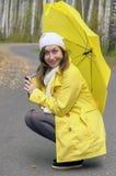 Mädchen im Herbstwald mit gelbem Regenschirm lizenzfreie stockbilder