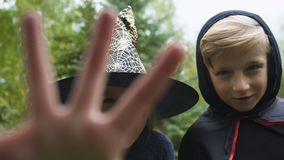 Mädchen im Hexenhut und -jungen im Umhang, der Kamera, Knurren gespenstisch, Halloween jagt stock video footage