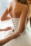 Mädchen im Hochzeits-Kleid zurück sehen an Braut-Abnutzungs-Weiß stockbild