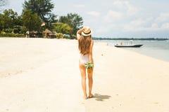 Mädchen im Hut, der Ananas auf dem Strand hält Lizenzfreies Stockfoto