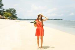 Mädchen im Hut, der Ananas auf dem Strand hält Lizenzfreie Stockfotos