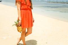 Mädchen im Hut, der Ananas auf dem Strand hält Stockfotos