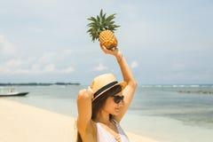 Mädchen im Hut, der Ananas auf dem Strand hält Stockfoto