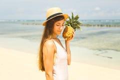 Mädchen im Hut, der Ananas auf dem Strand hält Lizenzfreie Stockbilder