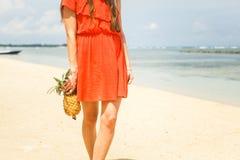 Mädchen im Hut, der Ananas auf dem Strand hält Lizenzfreie Stockfotografie