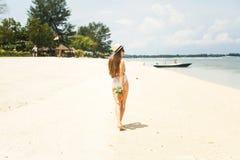 Mädchen im Hut, der Ananas auf dem Strand hält Lizenzfreies Stockbild